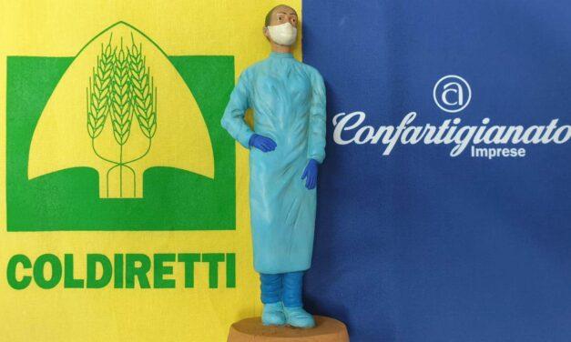 domani a cagliari alle ore 10.00, Confartigianato e Coldiretti di Cagliari consegnano al Vescovo Baturi la statuina dell'operatrice sanitaria anti-Covid, munita di mascherina.